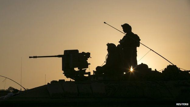 Israeli soldiers are seen atop an armoured personnel carrier (APC) near the border with Gaza July 30