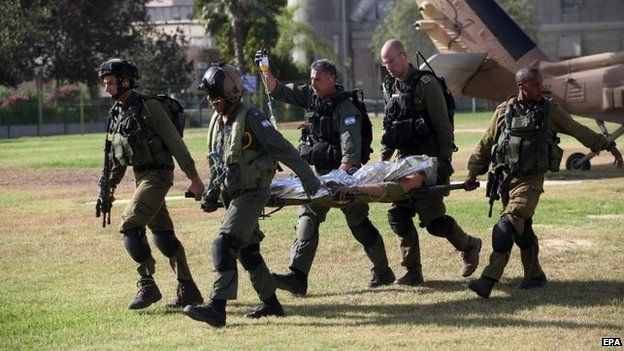 Israeli troops carry soldier wounded in Gaza, 30 July