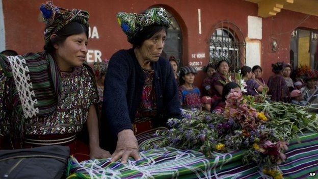 Relatives sit next to the coffin of Miguel Brito, one of 31 villagers massacred in 1982, during their burial in Santa Maria Nebaj, Guatemala, 30 July 2014