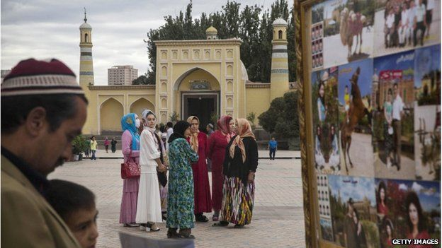 An Uighur man and his son look at photos as women stand in front of the Id Kah Mosque, China's largest mosque, on 31 July 2014 in Kashgar, Xinjiang Province, China.