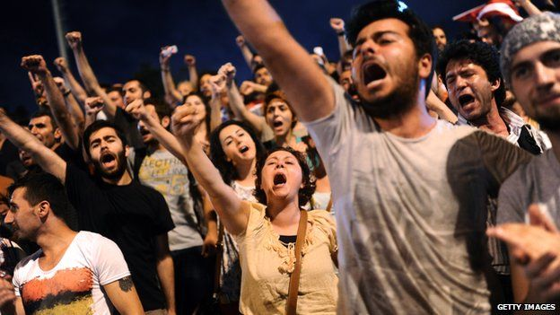 Turkish anti government protesters chant slogans at the entrance of Gezi park in July 2013