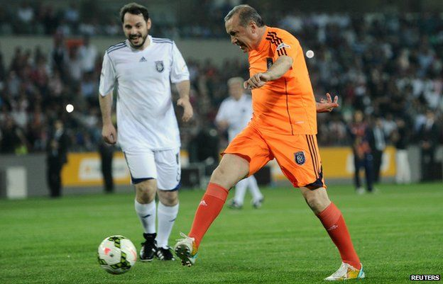 Turkish Prime Minister Recep Tayyip Erdogan kicks the ball during an exhibition football match in Istanbul on 26 July 2014