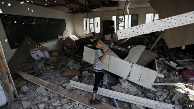 A displaced Palestinian child stands in a classroom, at the Abu Hussein UN school in Jabaliya, Gaza