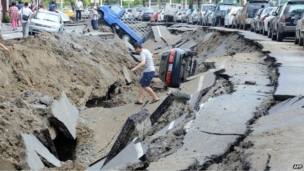 A resident crosses a damaged road in Kaohsiung on 1 August 2014