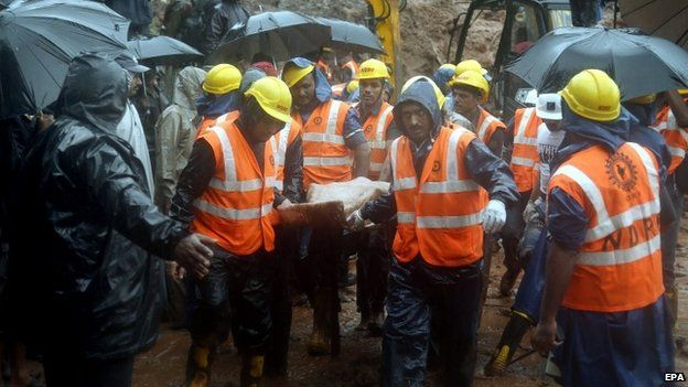 Members of an Indian National Disaster Response Force (NDRF) team carry a body at the site of a landslide in Malin village, Pune district, Maharashtra, India, 31 July 2014