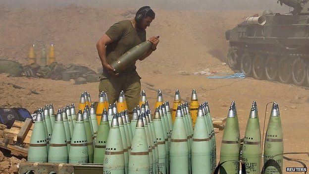 An Israeli soldier carries a shell at a mobile artillery unit that is firing at the Gaza Strip - 1 August 2014