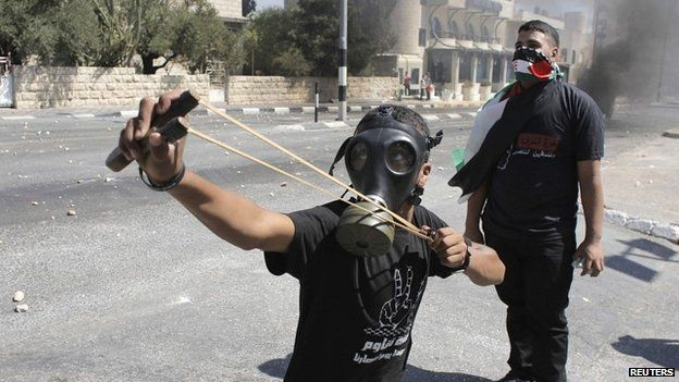 A Palestinian protester uses a slingshot during clashes with Israeli border police in the West Bank - 1 August 20134