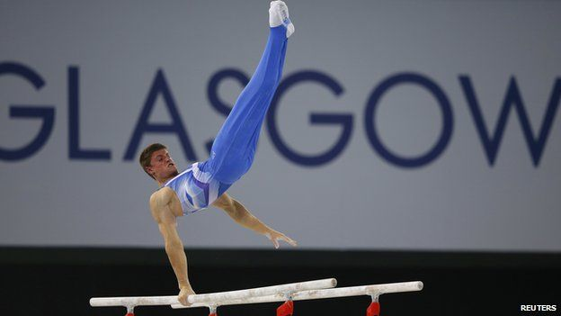 Frank Baines of Scotland performs on the parallel bars during the men's gymnastics team final