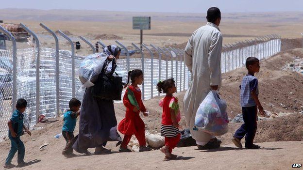 Members of an Iraqi displaced family, who fled violence in the northern city of Tal Afar, carry bags as they arrive at Khazer refugee camp near the Kurdish checkpoint of Aski kalak, 40 km West of Arbil, the capital of the autonomous Kurdish region of northern Iraq on July 27, 2014