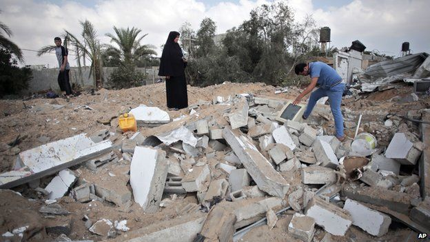 Palestinians search through rubble of a destroyed house