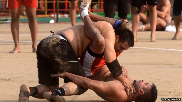 A Danish kabaddi player (top) is tackled by his Canadian opponent during the 4th World Cup Kabaddi Punjab 2013 tournament