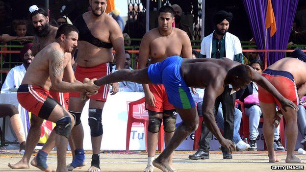 A Sierra Leone kabaddi player (R) is tackled by a British opponent during the 4th World Cup Kabaddi Punjab 2013