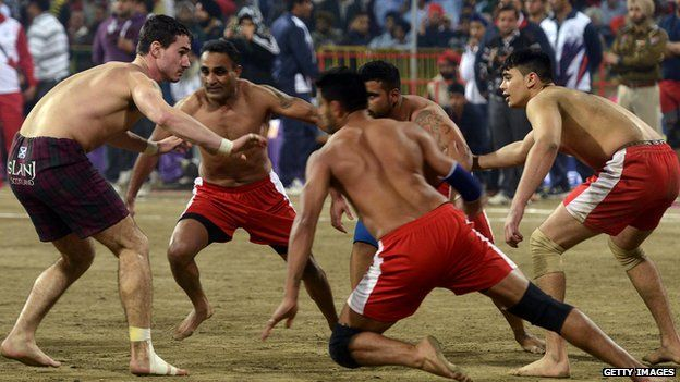 A Scotland player (L) attempts to tag his Canada opponent during the 4th World Cup Kabaddi Punjab 2013 tournament
