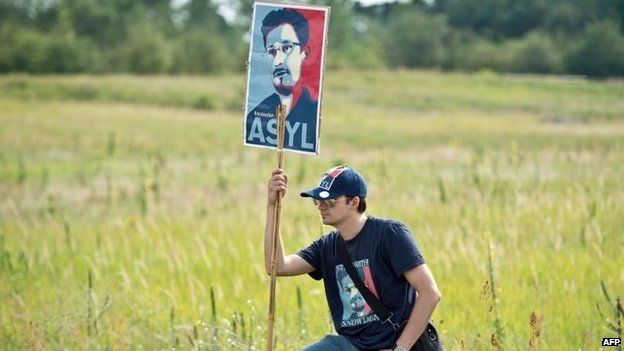 A man holds up a placard featuring US intelligence leaker Edward Snowden during a protest march near Darmstadt, central Germany 26 July 2014