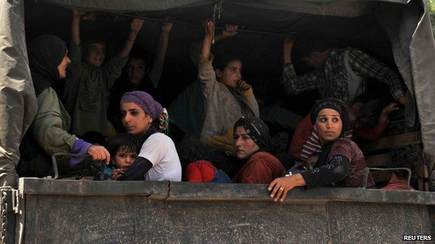 Syrian refugees sit in a Lebanese Army truck after fleeing the violence in Arsal, in Al-Labwa in eastern Bekaa Valley