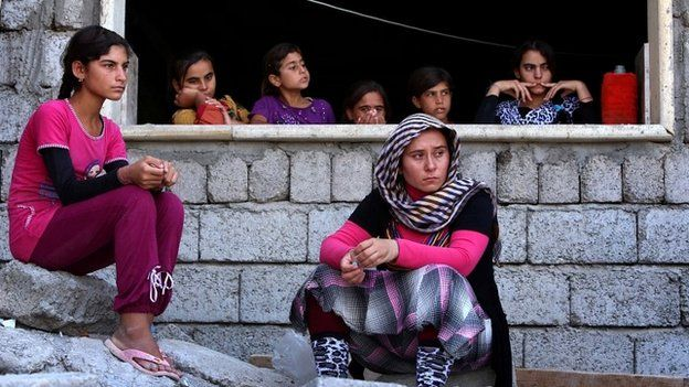 Yazidi women who fled the violence in the northern Iraqi town of Sinjar, sit at a shelter in the Kurdish city of Dohuk - 5 August 2014