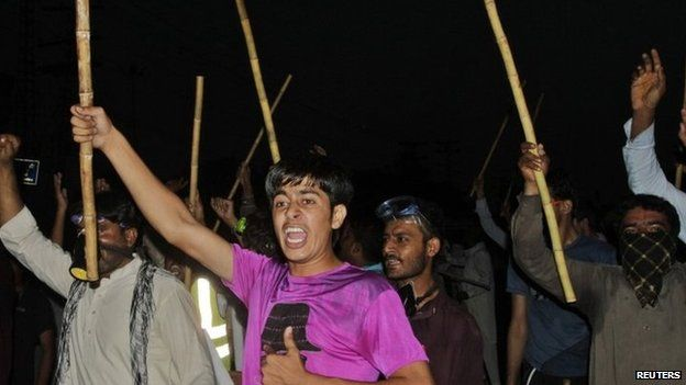 Supporters of Tahirul Qadri, leader of political party Pakistan Awami Tehreek (PAT), chant slogans as they wave sticks during a protest in Lahore 8 August 2014