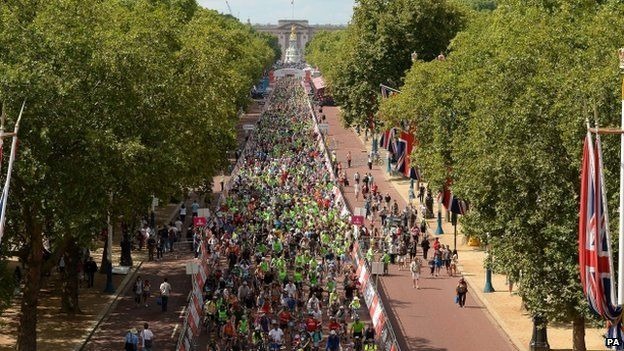 Cyclists make their way down The Mall from Buckingham Palace towards Admiralty Arch