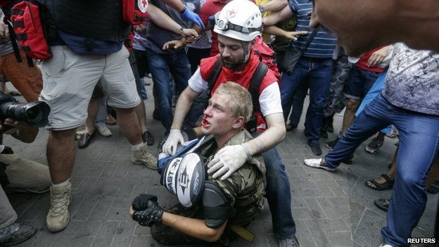 A protester receives medical treatment after clashes with municipal workers and volunteers at Independence Square in Kiev August 9