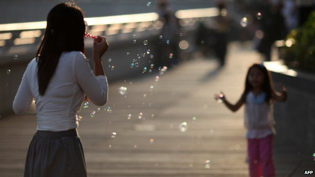 Children play with bubbles on a sunny afternoon in Tokyo, Japan on 9 April, 2012
