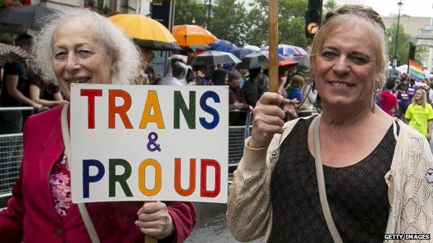"""Two people at Pride in the UK, one holding a """"Trans & Proud"""" sign"""