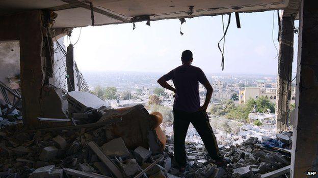 Palestinian man in rubble of apartment complex, Gaza