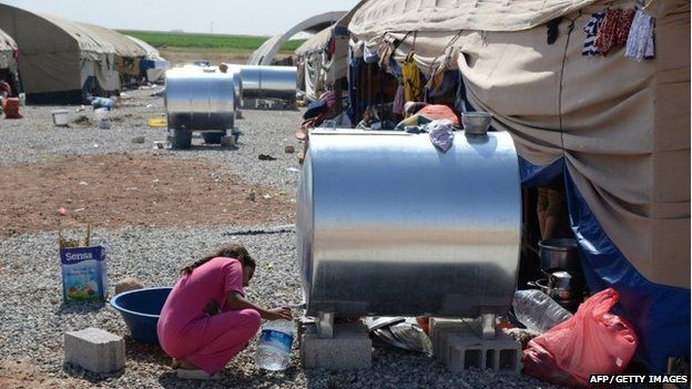 An Iraqi girl collects water from a water container