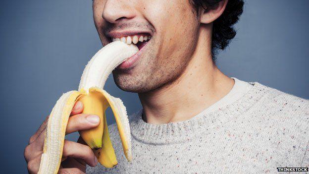 man consuming a banana