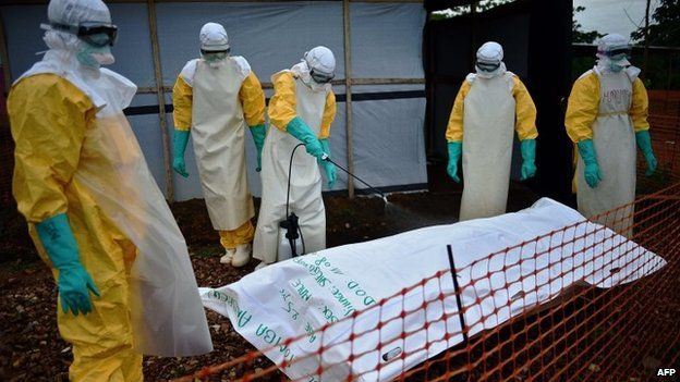 Medecins Sans Frontieres (MSF) medical workers disinfect the body bag of an Ebola victim at the MSF facility in Kailahun, Sierra Leone, 14 August 2014