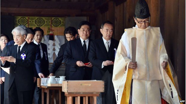 Japanese lawmakers follow a Shinto priest during a visit to the controversial Yasukuni shrine on 15 August 2014 to honour the country's war dead on the 69th anniversary of Japan's surrender in World War II, in Tokyo.