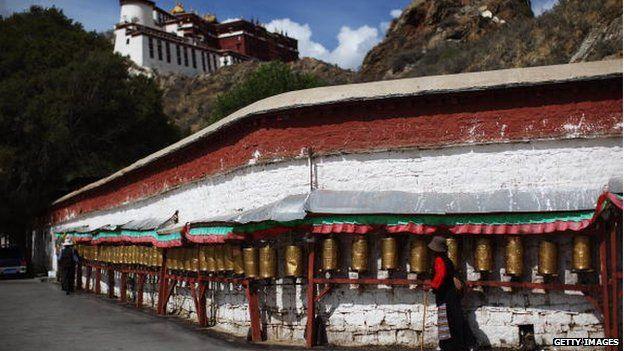 A Tibetan pilgrim spins prayer wheels on the pathway below the Potala Palace on 19 June 2009 in Lhasa, Tibet