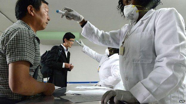 Kenyan health officials take the temperatures of passengers arriving at the Jommo Kenyatta International Airport - 14 August 2014