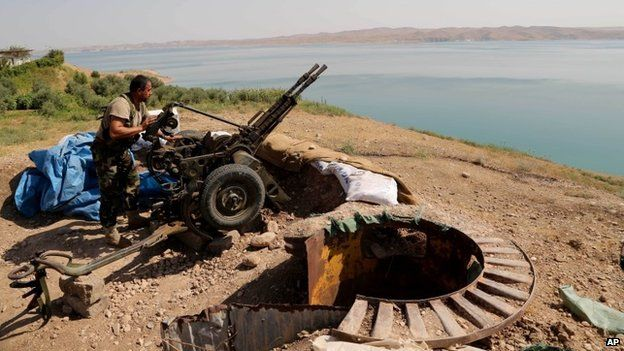 A Kurdish peshmerga fighter prepares his weapon at his combat position near the Mosul Dam at the town of Chamibarakat outside Mosul, Iraq, Sunday, Aug 17