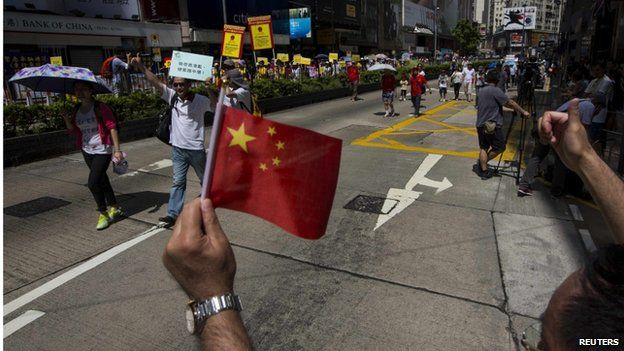 A pro-Beijing protester waves a Chinese national flag and thumbs up to other supporting protesters during a march in the streets to demonstrate against a pro-democracy Occupy Central campaign in Hong Kong 17 August 2014
