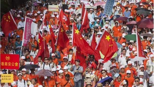 """Pro-China protestors, opponents of the pro-democracy """"Occupy Central"""" movement, march through the streets of Central District, Hong Kong, China, 17 August 2014."""