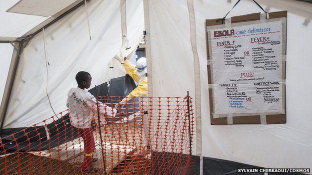 A MSF nurse accompanies a sick child