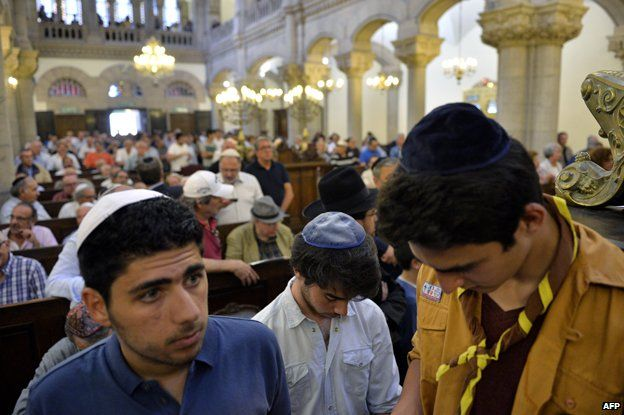 Men wearing skullcaps attend a praying ceremony, on July 31, 2014 inside Lyon's synagogue, in south-eastern France