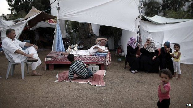 Displaced Palestinian families rest in the grounds of a makeshift camp inside the Al-Shifa hospital gardens in Gaza City