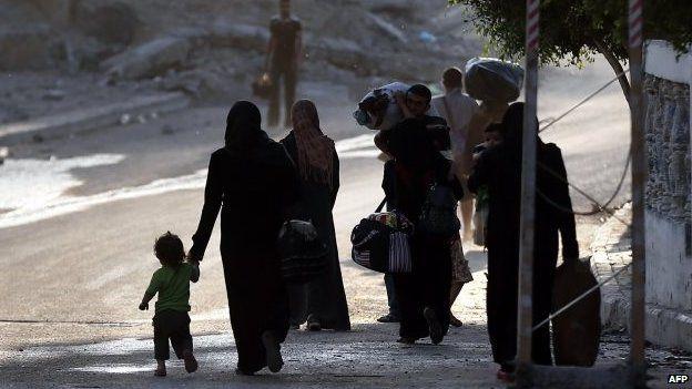 Palestinians flee with their belongings from the Shejaiya neighborhood of Gaza City