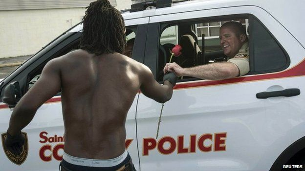 Resident John West (L) hands a rose to a police officer, showing his appreciation with help in cleanup efforts in Ferguson, Missouri, August 19