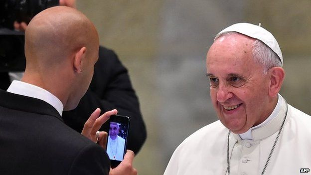 A San Lorenzo player takes a picture of Pope Francis, before his general audience in the Paul VI hall at the Vatican on 20 August, 2014.
