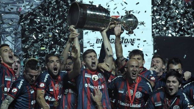 San Lorenzo players hold up the trophy after winning the Copa Libertadores 2014 final second leg football match against Nacional in Buenos Aires on 13 August, 2014