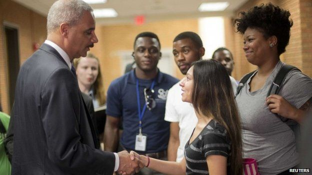 Attorney General Eric Holder shakes hands with Bri Ehsan, 25, following his meeting with students at St. Louis Community College Florissant Valley in Ferguson, Missouri 20 August 2014