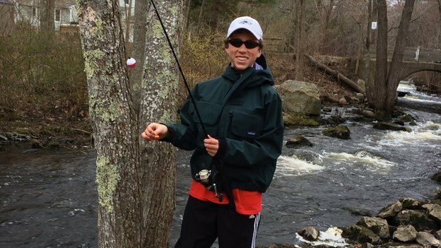 Christopher Herndon, an adolescent boy, is in a river wearing fishing gear and holding a fishing rod.