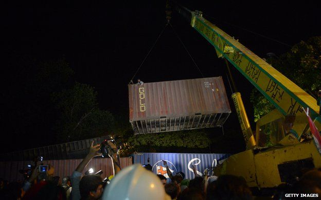 A crane moving shipping containers at night