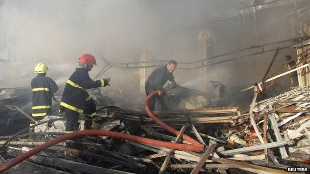 Firefighters work to extinguish flames at the scene of a car bomb attack in Kirkuk