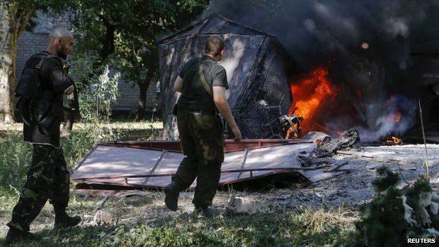 Armed pro-Russian separatists walk in front of garages set ablaze by what locals say was recent shelling by Ukrainian forces in Donetsk (23 August 2014)