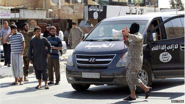 An Islamic State militant uses a loud-hailer to announce that Tabqa air base has fallen, in Raqqa city August 24