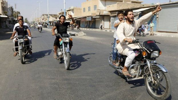 Residents of Tabqa city and Islamic State militants tour the streets in celebration after Islamic State militants took over Tabqa air base, in nearby Raqqa city August 24,