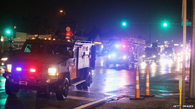 A convoy of armoured personnel carriers (APC) carrying county police arrive after Missouri State Highway Patrol officers were taunted by demonstrators during a protest over the shooting of Michael Brown on August 15, 2014 in Ferguson, Missour